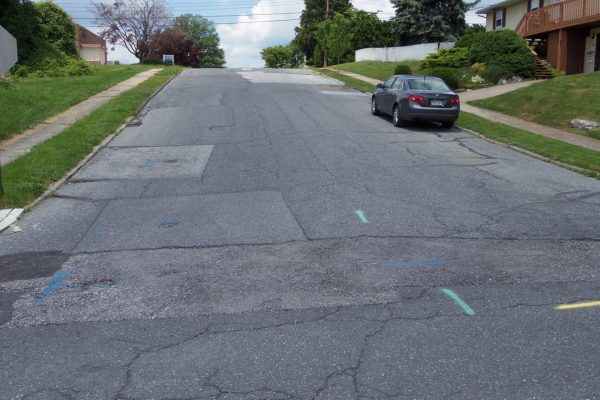 This residential street has seen many trench restorations and new asphalt overlays. the curb reveal is almost non existing allowing storm water to run into the roadway or over the curbs. The roadway again has many unattended cracks and depressions can be seen in the upper portion of the roadway.